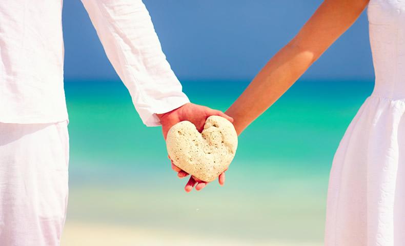 ビーチでハートの石を持つカップル