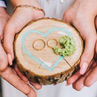 結婚指輪を持つカップルの手
