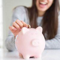 ブタの貯金箱にコインを入れる女性